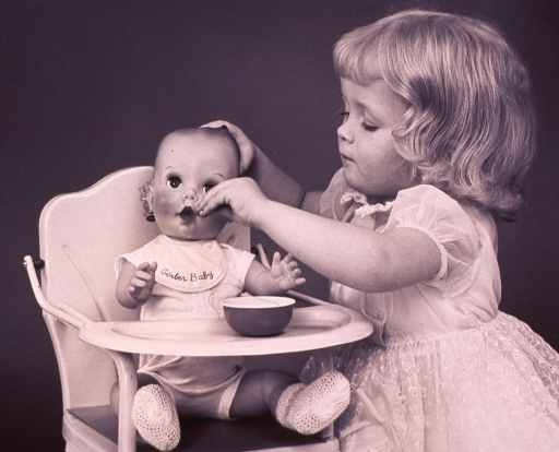 <p>A little girl is feeding her doll which is sitting in a toy highchair.</p>