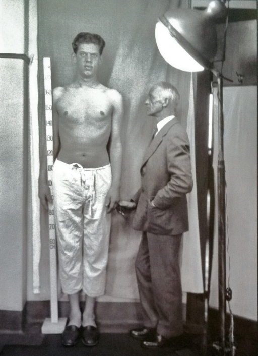 Harvey Cushing posing with a patient with acromegaly. Unlike other medical portraiture traditions, Cushing stands with his subject and gently makes his presence known to both viewer and patient.