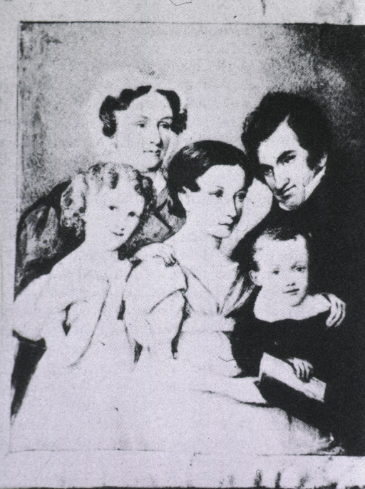 <p>Three quarters length,  holding child, with wife and two other children to his right.</p>