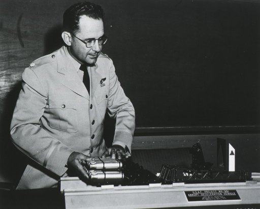 <p>Lt. Col. Stapp demonstrating model of the abrupt deceleration vehicle, to explain how he established a new ground speed record of 421 miles per hr.</p>