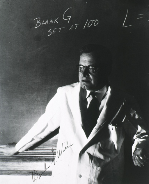 <p>Three quarter length, standing with back to black board, wearing white coat.</p>