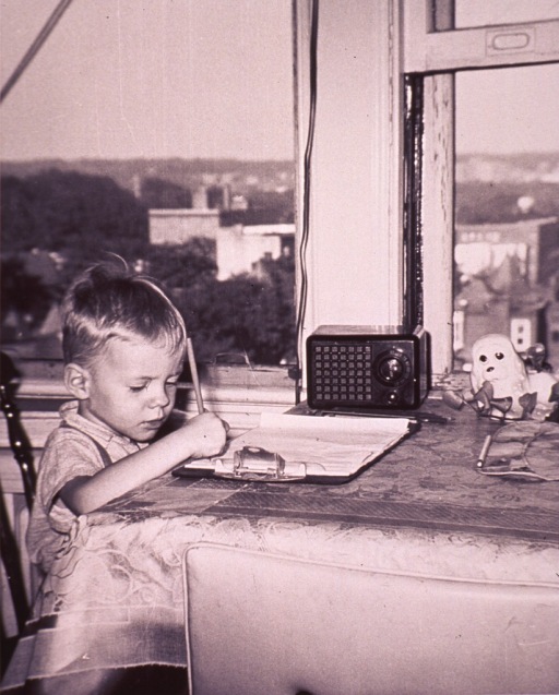 <p>A child is sitting at a table writing on papers on a clipboard; there is a radio on the table.</p>