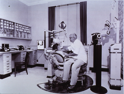 <p>Interior view: chair, dental unit, and x-ray machine.  Dentist is attending to a patient in the chair.</p>