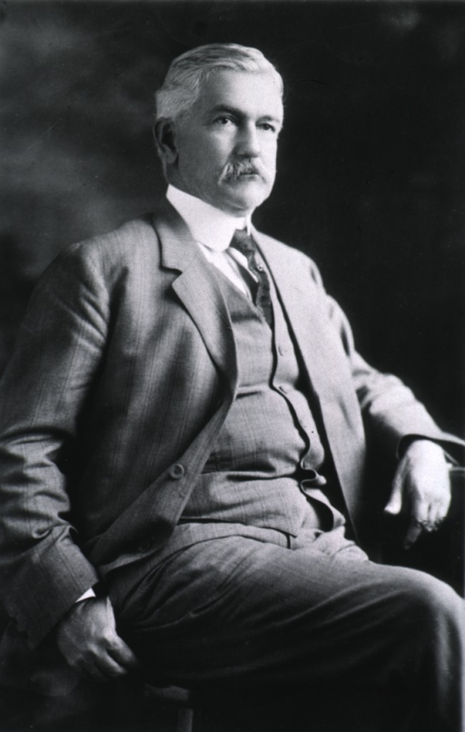 <p>Three-quarter length, seated, right pose; wearing suit.</p>