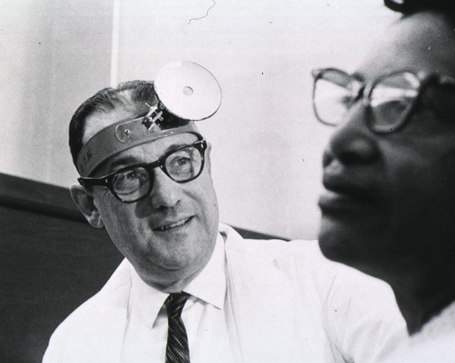 <p>Head and shoulders, full face; wearing lab coat and reflector; wearing glasses; in E.N.T. clinic with patient in foreground.</p>