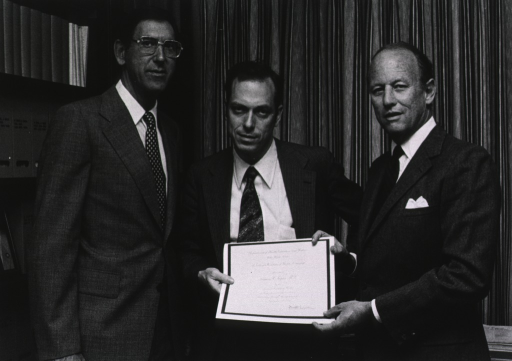 <p>Robert Goldberger, deputy director for science at the National Institutes of Health (NIH), is standing next to Solomon H. Snyder, of Johns Hopkins University, who is holding an award with Donald S. Fredrickson, director of the NIH.  There is a bookcase behind Dr. Goldberger.</p>
