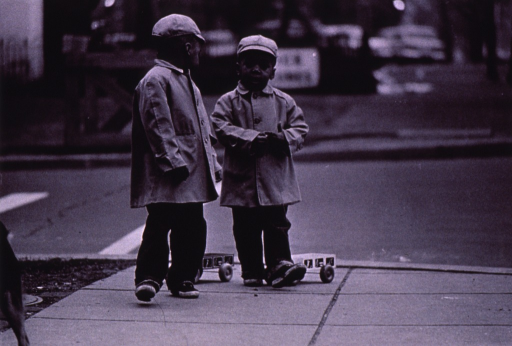 <p>Two children, with pull toys, are walking along the sidewalk.</p>