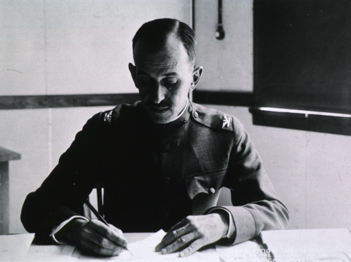 <p>Half-length, seated at desk, full face; wearing uniform; writing.</p>