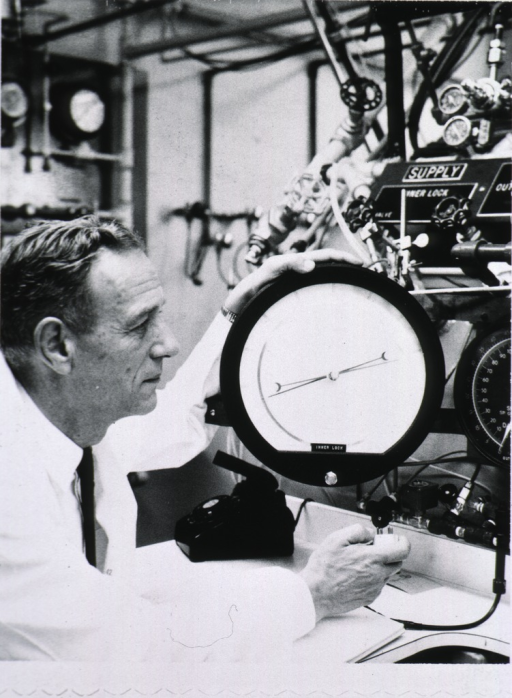 <p>Half length, right profile; in laboratory coat; in lab, reading gauge on some type of equipment (pressure chamber?).</p>