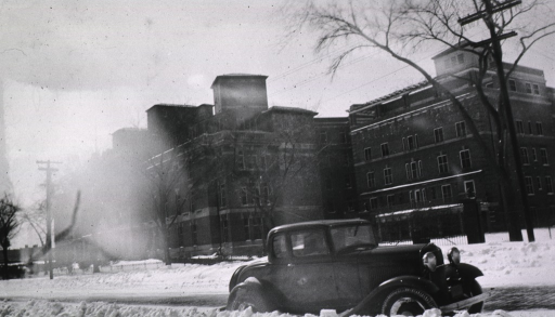 <p>Exterior of the hospital with a car in the foreground.</p>
