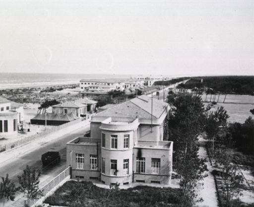 <p>Bird's-eye view of a station hospital in Leghorn (i.e. Livorno), Italy. Buildings line either side of a paved road that cuts through sandy terrain and runs parallel to a beach. A military vehicle is shown driving down the road. In the distance the Ligurian Sea is visible.</p>
