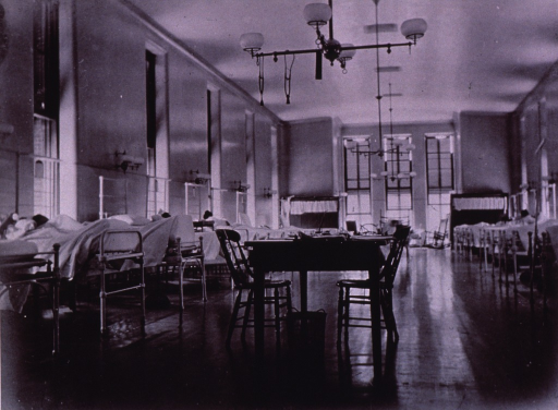 <p>Interior view of ward: a table with two chairs is in the center aisle (nurses' station?); beds line the walls on both sides of the ward. Two stethoscopes hang from a light fixture over the table.</p>