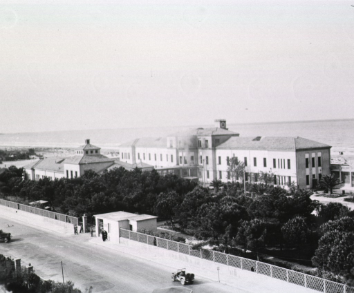 <p>Bird's-eye view of a station hospital in Leghorn (i.e. Livorno), Italy. Two buildings rise behind a forest of trees and a fence that abuts a paved road. Military personnel stand at the gate as military vehicles drive down the road. In the distance the Ligurian Sea is visible.</p>