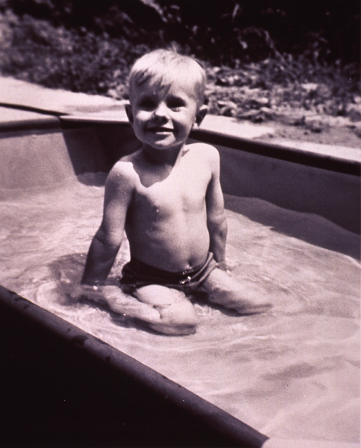 <p>A child is sitting in a wading pool.</p>