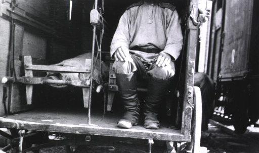 <p>A soldier(?) sits on a litter in a Russian wagon ambulance; a second litter is beside him.</p>