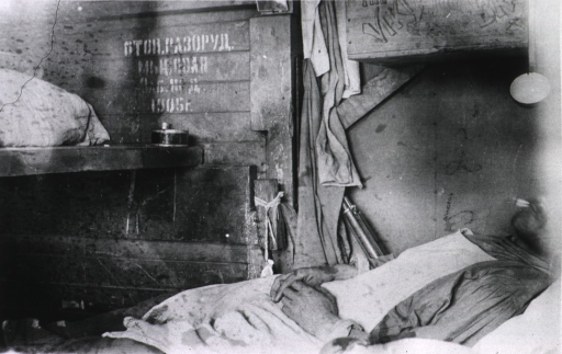 <p>A soldier(?) lies in a bunk, smoking, in a railroad freight car that was used for hospital transport.</p>
