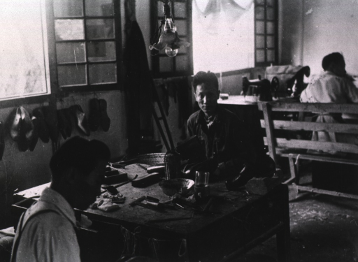 <p>Interior view: on the wall are shoe molds; under the window is a sewing machine; two men are sitting at a table on which tools are lying.</p>