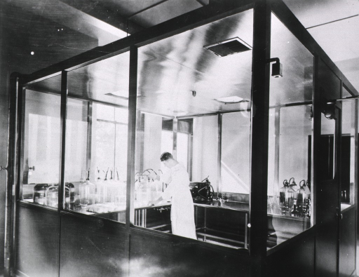 <p>Interior view: a man is standing in a room next to tables on which there are large jars and a piece of equipment with a fan belt; air vents are in the ceiling; lighting is recessed; the room is in front of windows to the outside.</p>