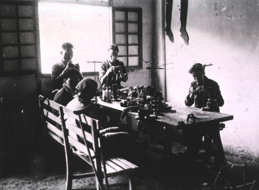 <p>Interior view: some men are sitting sewing, others are standing, around a table on which thread and other material is lying.</p>