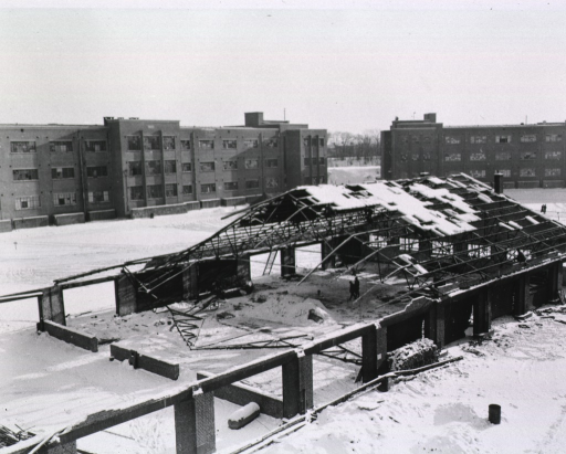 <p>A one-story building stands in ruins.  The ceiling has been mostly destroyed and snow covers the ground of the building's exposed interior.</p>
