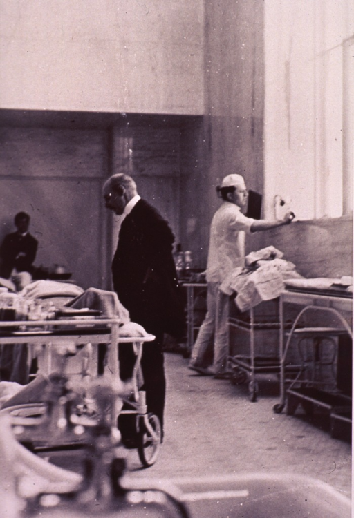 <p>Halsted standing, full length, left profile, next to a patient on a gurney.</p>