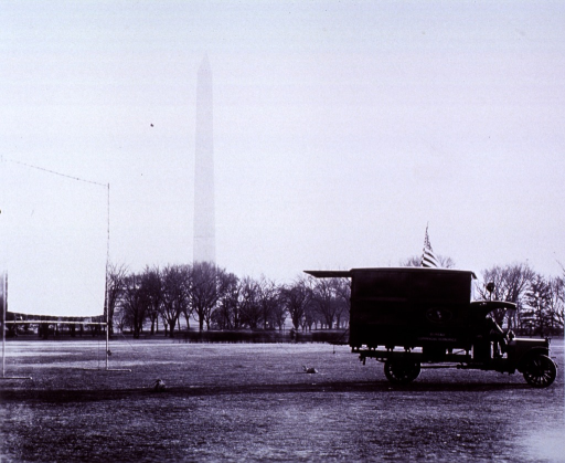 <p>A Commercial Economics Bureau motion picture outfit is in front of the Washington Monument.  A white screen stretched onto a stand is behind the truck.</p>