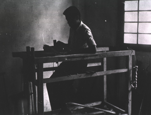 <p>Interior view: a man is sitting inside a wooden structure.</p>