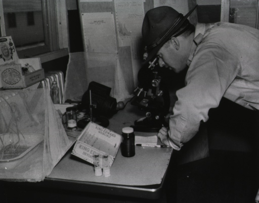 <p>A man in military uniform looks through a microscope at specimen on a slide in a military base laboratory.</p>