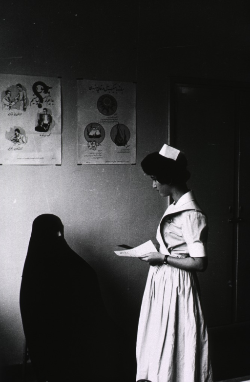 <p>A female nurse (right) in a nursing uniform (three-quarter length portrait, standing, facing left) is interviewing a prospective female patient (left) wearing a chador (three-quarter length portrait, sitting, facing right), the black robe worn by traditional Muslim women; on the wall behind them are two posters, the one on the left is concerned with treatment for tuberculosis.</p>