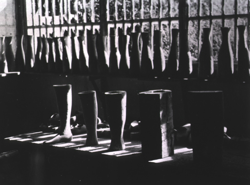 <p>Interior view: on the window sill is a row of bottle shaped structures; beneath the window is a table with five examples showing the stages involved in making an artificial leg from an undefined block to the foot to knee leg.</p>
