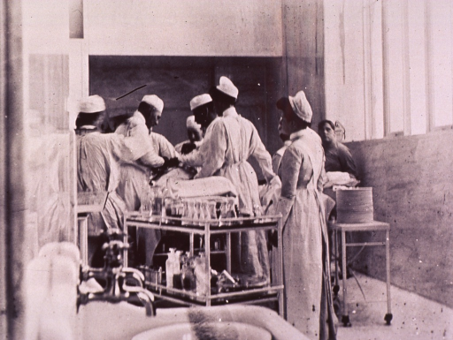 <p>Interior view of operating room: operation by Halsted and Finney is in progress; support staff and cart of supplies are in the foreground.</p>