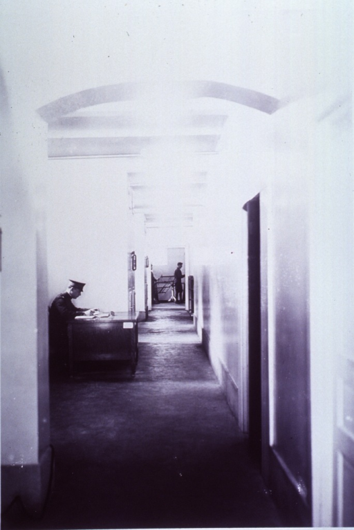 <p>Interior view: a soldier is sitting at a desk.  At the end of a hallway, through an open doorway, two men are standing by a drying rack.</p>