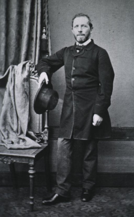 <p>Standing, full length, front pose, arm over chair, holding hat.</p>