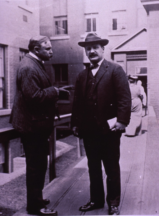 <p>Standing full length, Finney in right profile, and Smith turned slightly to the left, full face, and wearing a hat.</p>