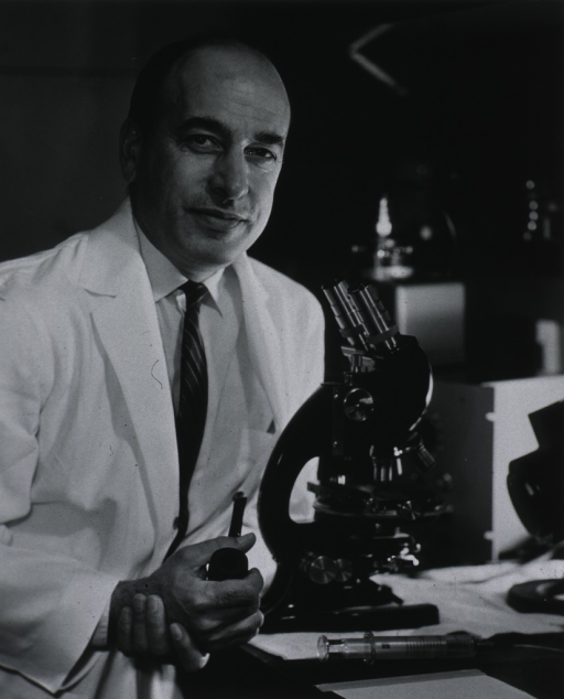 <p>Half-length, turned slightly to right, in lab coat in front of microscope, pipe in hand, hypodermic on table.</p>