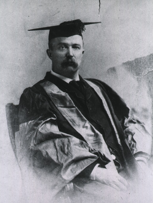 <p>Half-length, seated, wearing academic gown.</p>