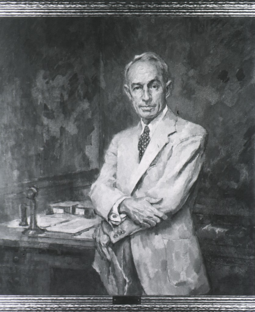 <p>Standing by table; arms crossed; white coat; full face.</p>