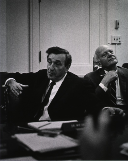 <p>Shows Dr. Jerome B. Wiesner and Dr. Douglas Bond seated at the conference table.</p>