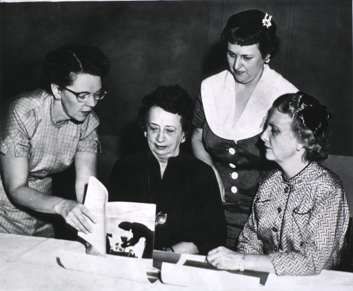 <p>View of four women looking at documents.</p>