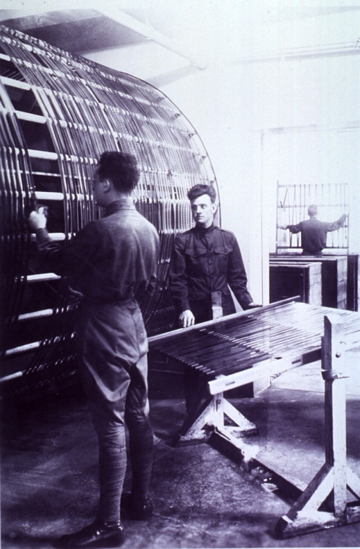 <p>Interior view: a soldier is facing a large drying rack while another soldier stands by smaller drying rack.  In the background is a third soldier facing a drying rack.</p>