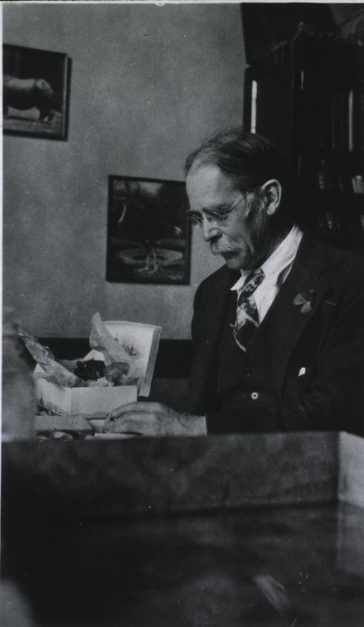 <p>Seated in his office, left pose.</p>