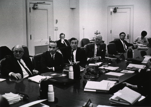 <p>Shows Dr. Anlyan, Dr Irvin M. London, Dr. Jerome B. Wiesner, Dr. Douglas Bond, Dr. Ronald W. Lamont-Havers and Mrs. Norma Nichols seated at the conference table.  In the background, is seated Mr. Clifford Johnson.</p>