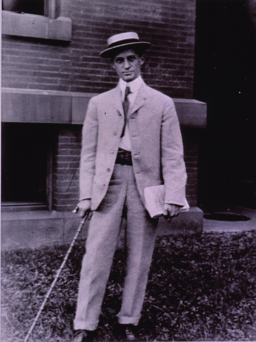 <p>Full length, standing, full face; wearing hat and holding a cane in right hand and a book in left.</p>