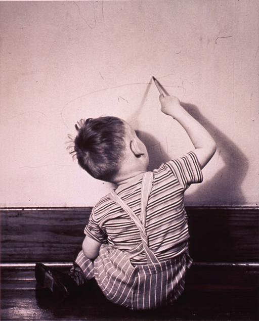 <p>A child is drawing on the wall with a pencil.</p>