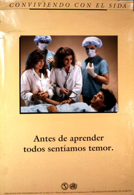 <p>A man is lying on a bed.  A woman in a white hospital jacket is holding his right hand, while another woman uses a stethoscope.  Behind the two women are two men, identically dressed in green scrub suits, surgical bonnets, masks, and gloves.</p>