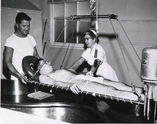 <p>Paraplegic patient being lowered into Hubbard tank for treatment.</p>