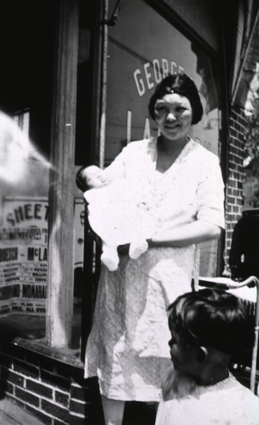 <p>A mother holds her infant in front of a store.  A small child is in the foreground.</p>