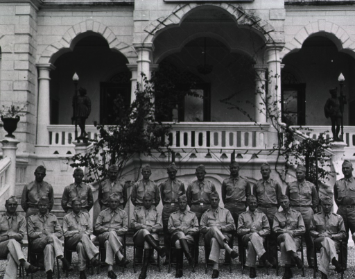 <p>Two rows of men in military uniform, the front row seated, the rear standing, pose outdoors in front of a balcony of an ornate edifice.  (The rightmost man seated in the front row, also identified on the verso, has been cropped from this print.)</p>