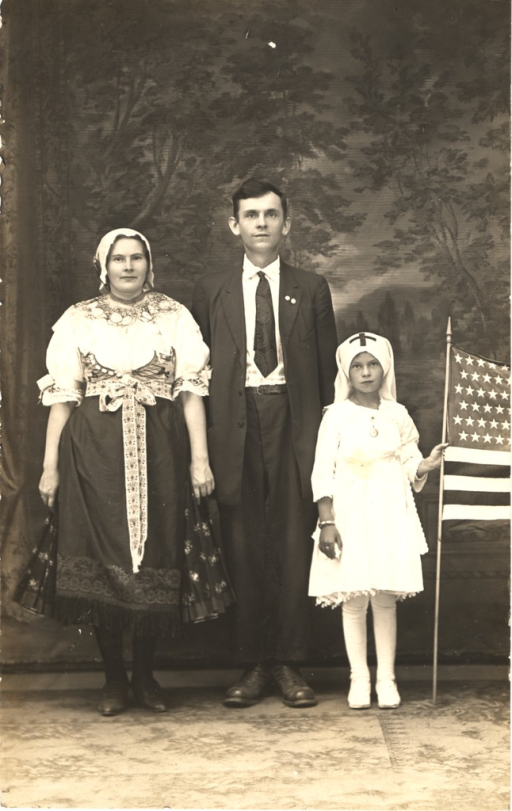 <p>Black and white photograph of an immigrant family. The young girl is dressed as a nurse and is holding an American flag.</p>