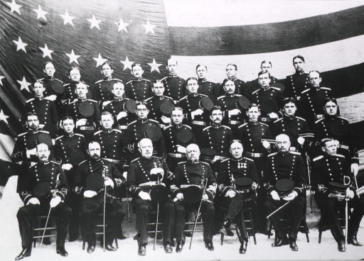 <p>Men in dress uniform are in front of a large American flag.  The men in the front row are holding their swords.</p>